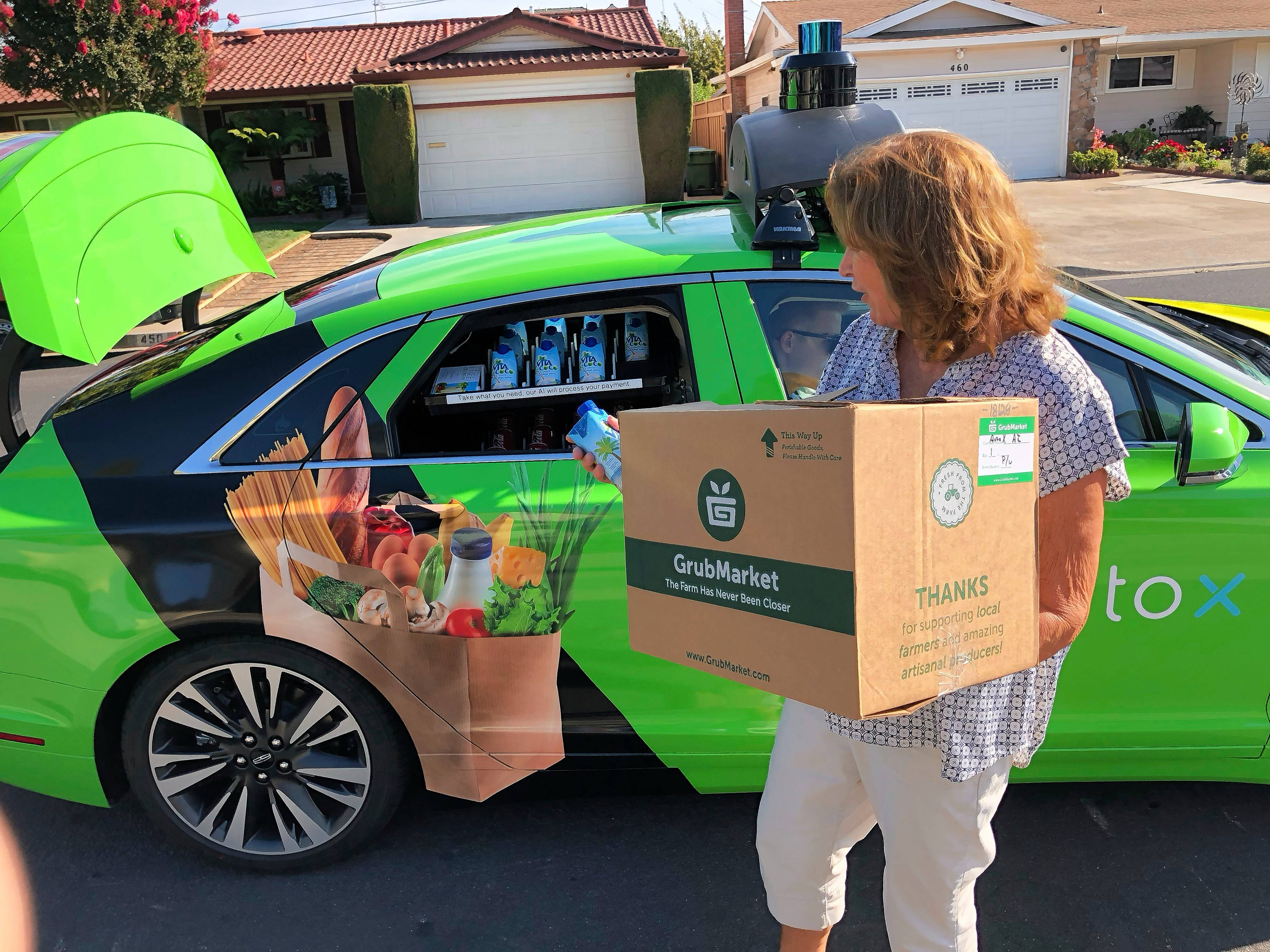 Customer Maureen Blaskovich grabs a coconut water from the back seat window of a self-driving car -- a Lincoln MKZ outfitted with technology by AutoX -- in San Jose, California. The company is partnering with grocery delivery startup GrubMarket in a pilot test to deliver groceries to shoppers near the company's headquarters.