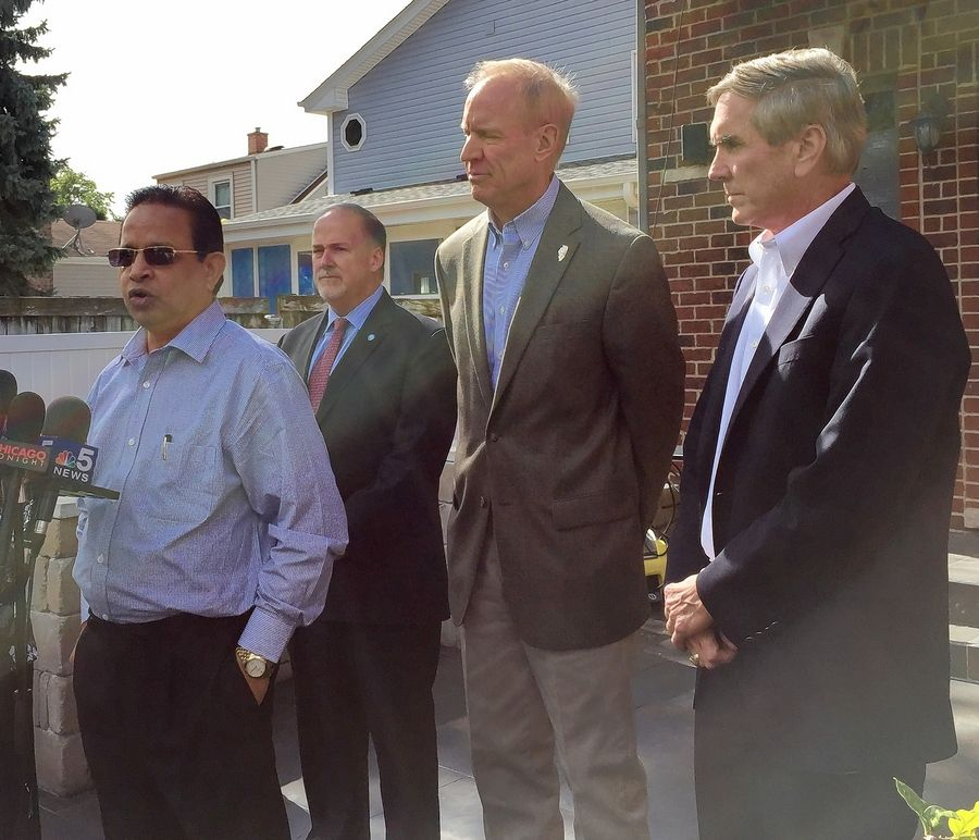 John Trivedi, left, speaks about high property taxes during a political event at his Des Plaines home where, behind him from left, Cook County Commissioner Sean Morrison, Gov. Bruce Rauner and Commissioner Tim Schneider called on the Cook County state's attorney to investigate an inspector general's report critical of a tax break given to Democratic candidate J.B. Pritzker.