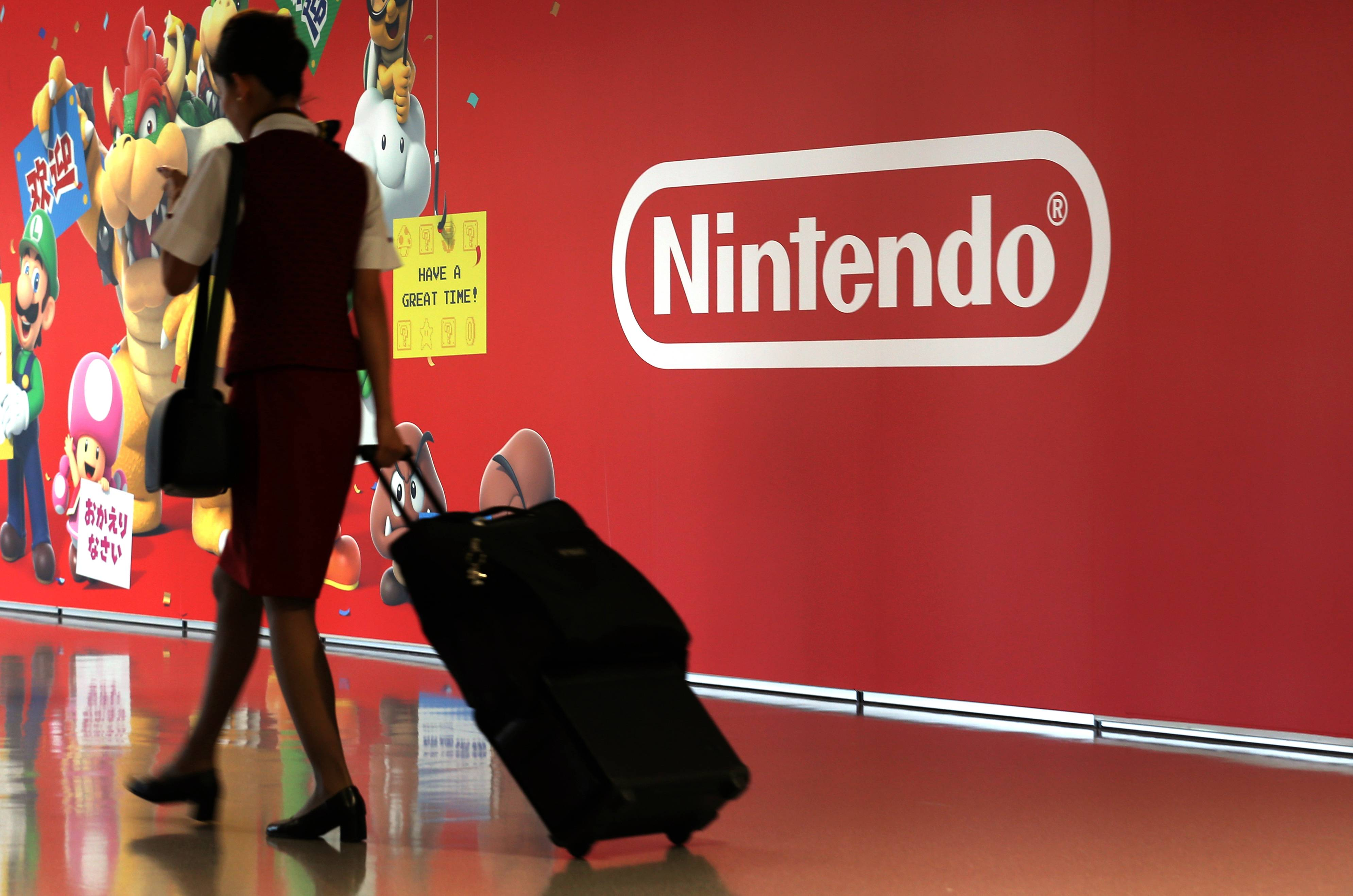 An airline employee walks past a mural featuring characters from Nintendo Co.'s Super Mario video games at Terminal 1 of Kansai International Airport in Japan.
