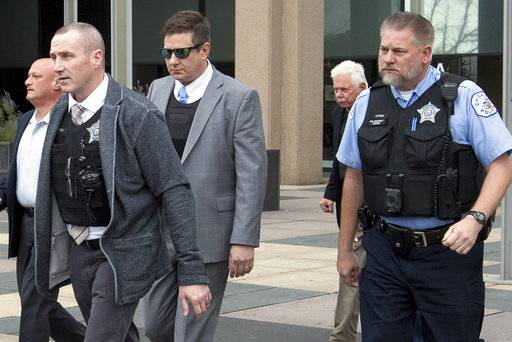 Chicago Police Officer Jason Van Dyke, wearing sunglasses, is escorted out of the Leighton Criminal Court Building in Chicago, Tuesday, Oct. 2, 2018, after testifying in his first degree murder trial for the shooting death of Laquan McDonald.
