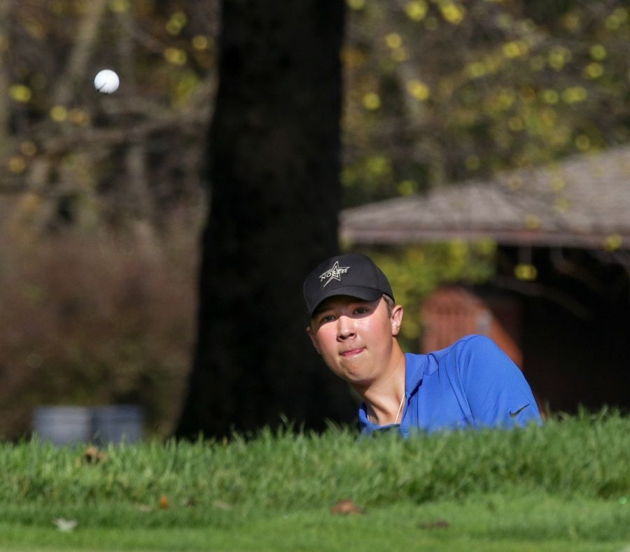 St. Charles North's Alex Lilly chips on the second green Monday.