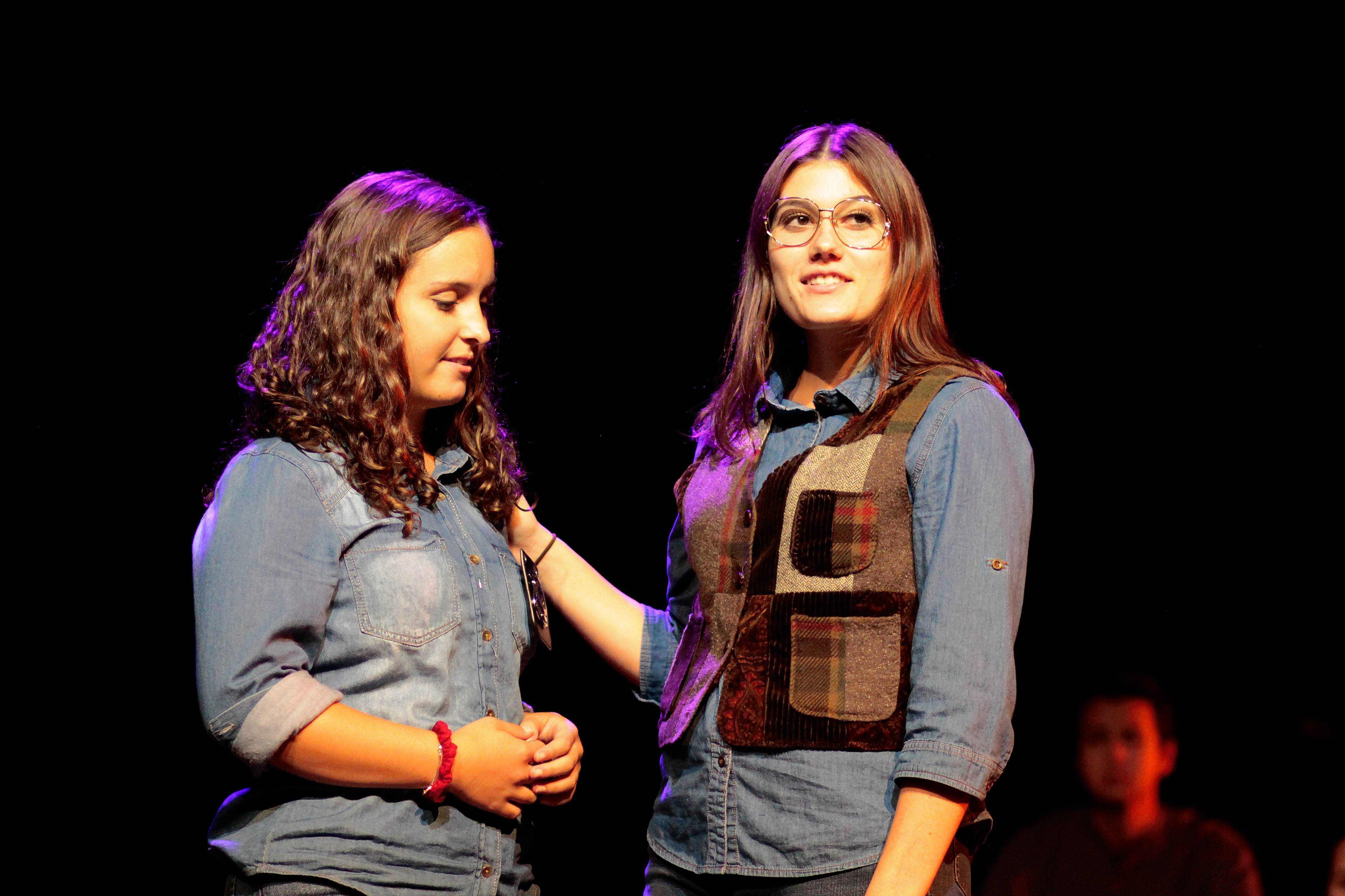 "From left, junior Megan Fisher and senior Emma Ambrosia, both of Cary, portray Reggie Fluty, the police office that responded to the 911 call; and Marge Murray, Reggie's mother, in the Cary-Grove High School production of ""The Laramie Project."""