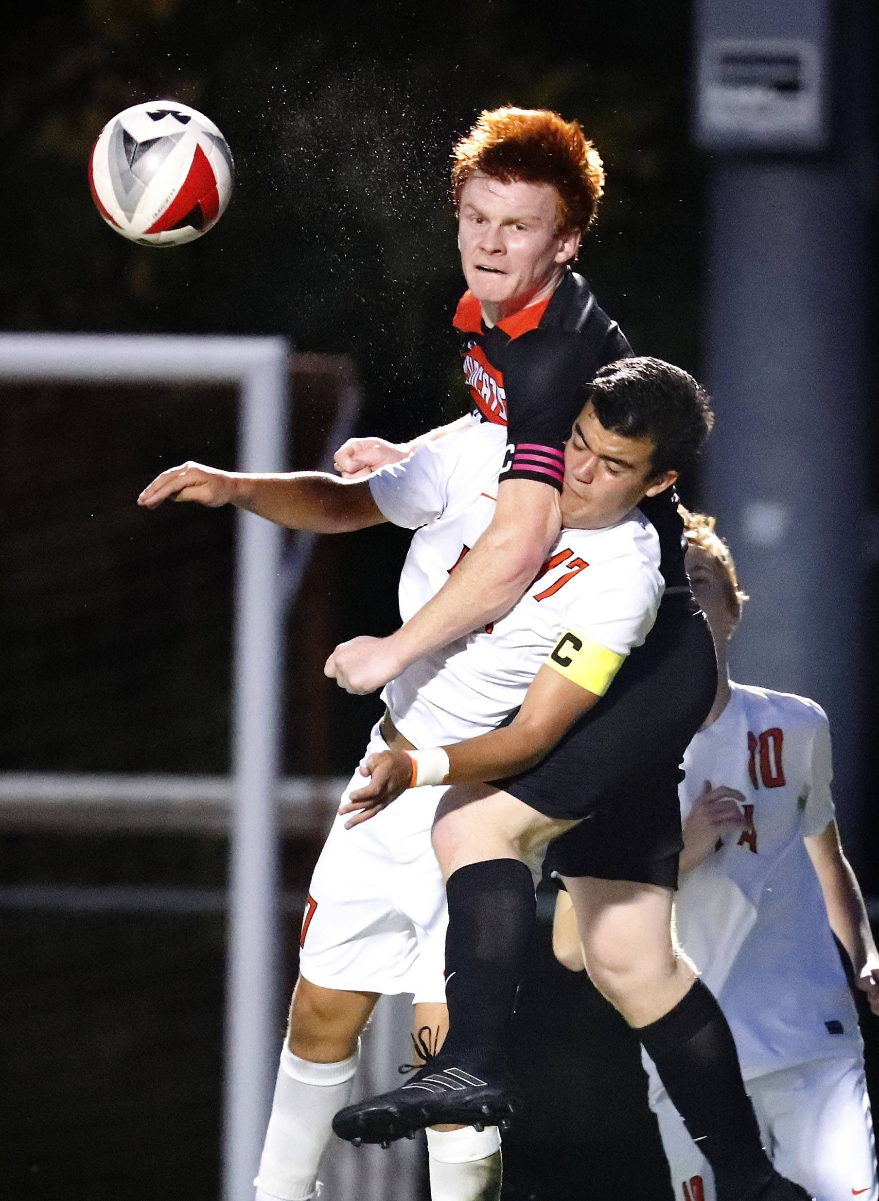 Libertyville's Evan Rasmussen, left, goes up for a header with Lake Forest Academy's Sergio Estrelles during their game Tuesday night in Libertyville.