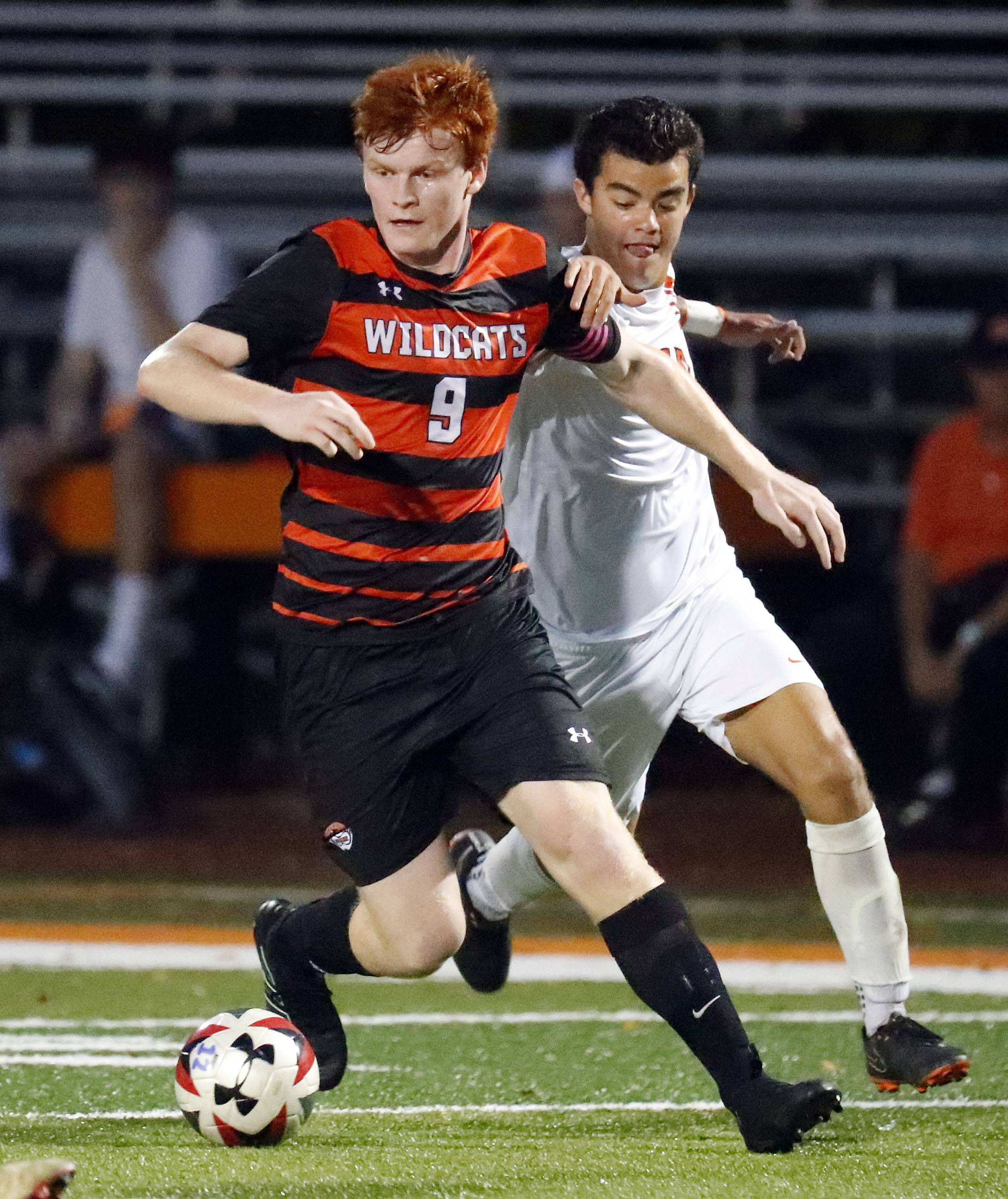 Libertyville's Evan Rasmussen, left, drives on Lake Forest Academy's Sergio Estrelles during their game Tuesday night in Libertyville.