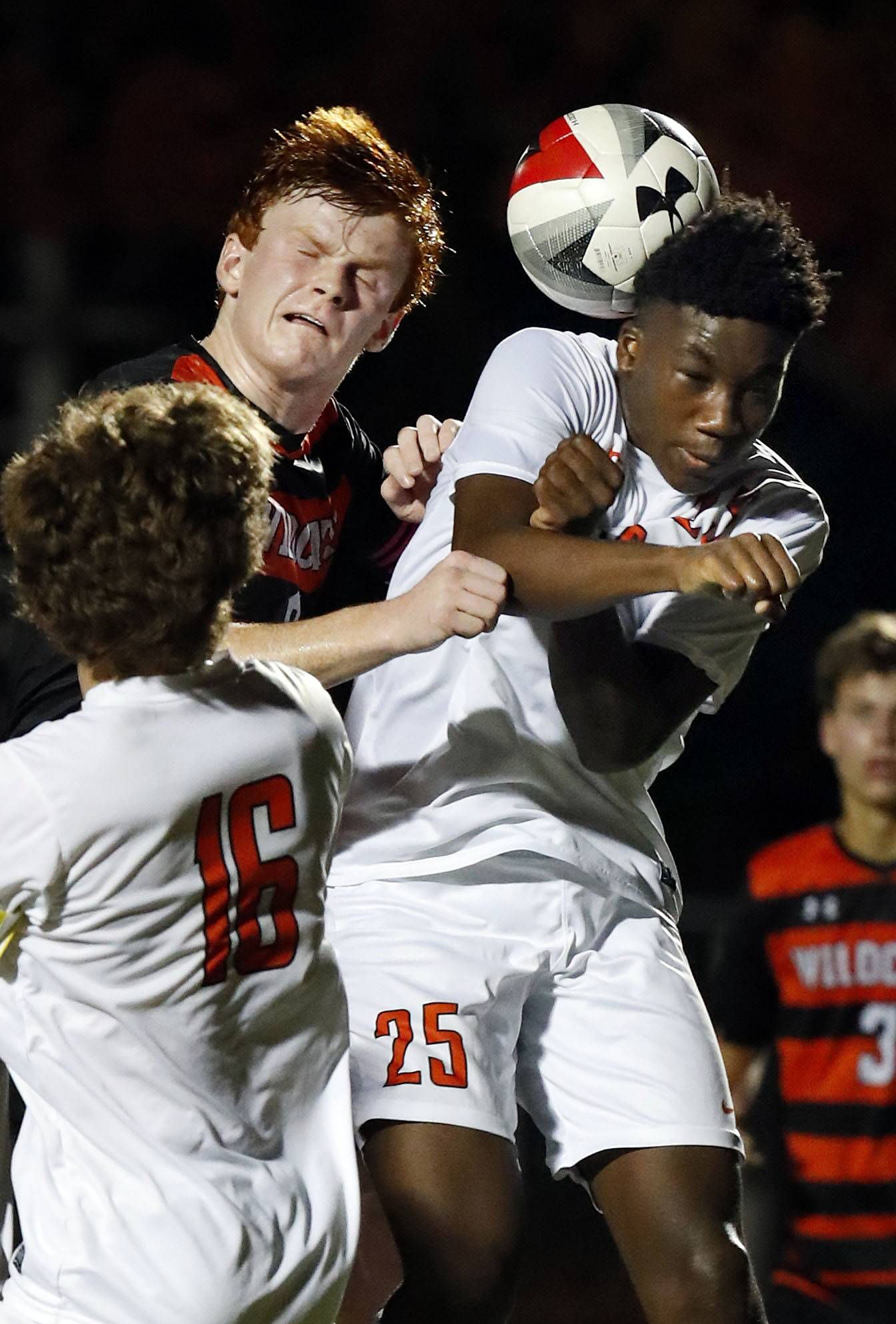 Libertyville's Evan Rasmussen, left, goes up for a header with Lake Forest Academy's David Oluwole during their game Tuesday night in Libertyville.