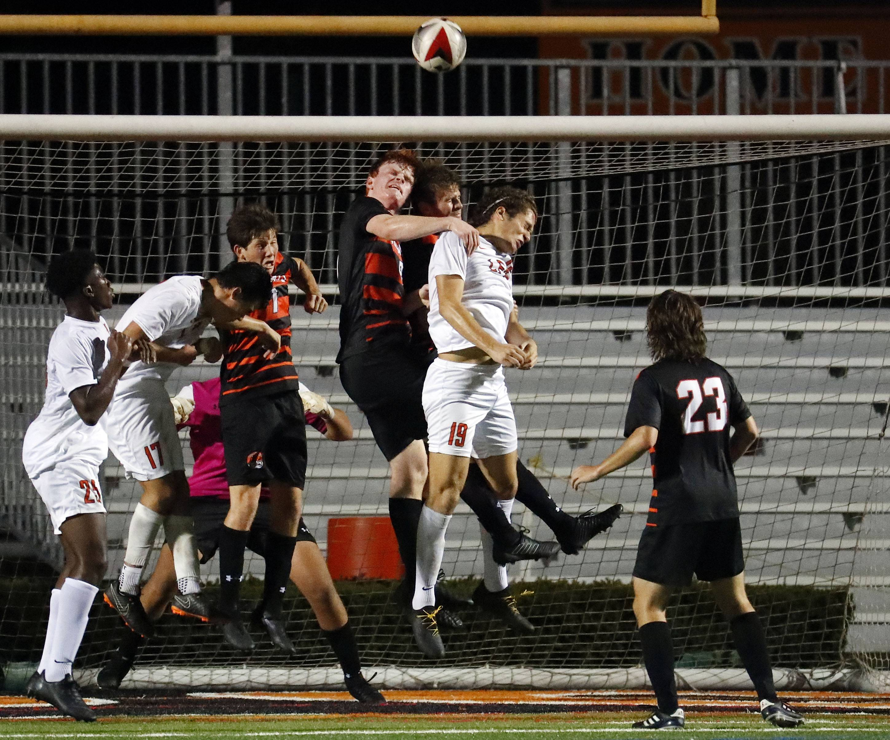 Players go up for a crossed ball as Libertyville took on Lake Forest Academy Tuesday night in Libertyville.