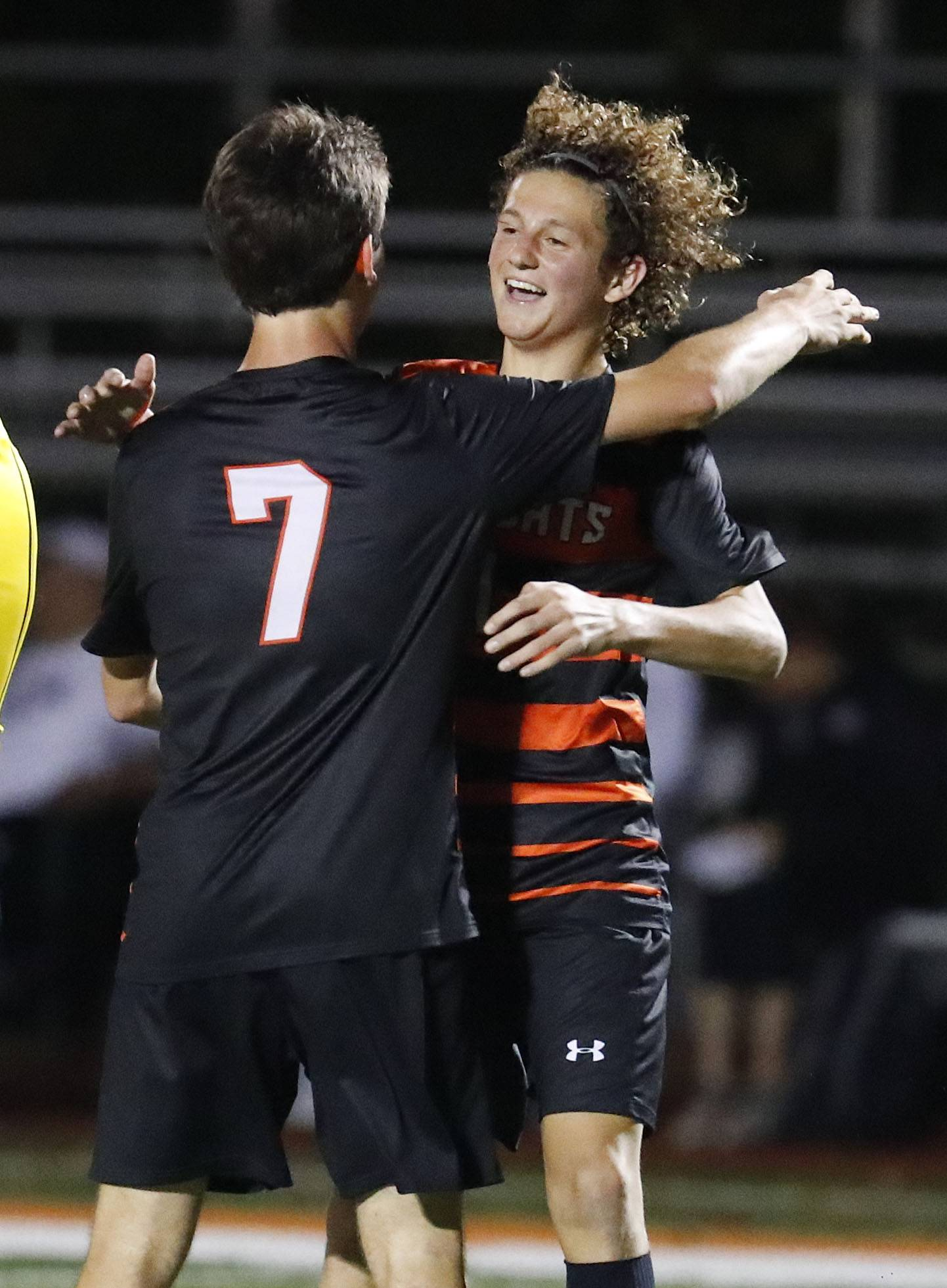 Libertyville's Mickey Reilly, right, gets a hug from Tanner Kelly after scoring during their game against Lake Forest Academy Tuesday night in Libertyville.