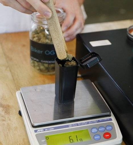 In this Tuesday, Oct. 2, 2018, photo, marijuana buds are weighed for a customer at Utopia Gardens, a medical marijuana dispensary, in Detroit. Michigan and North Dakota, where voters previously authorized medical marijuana, will decide now if the drug should be legal for any adult 21 and older. They would become the 10th and 11th states to legalize so-called recreational marijuana since 2012.