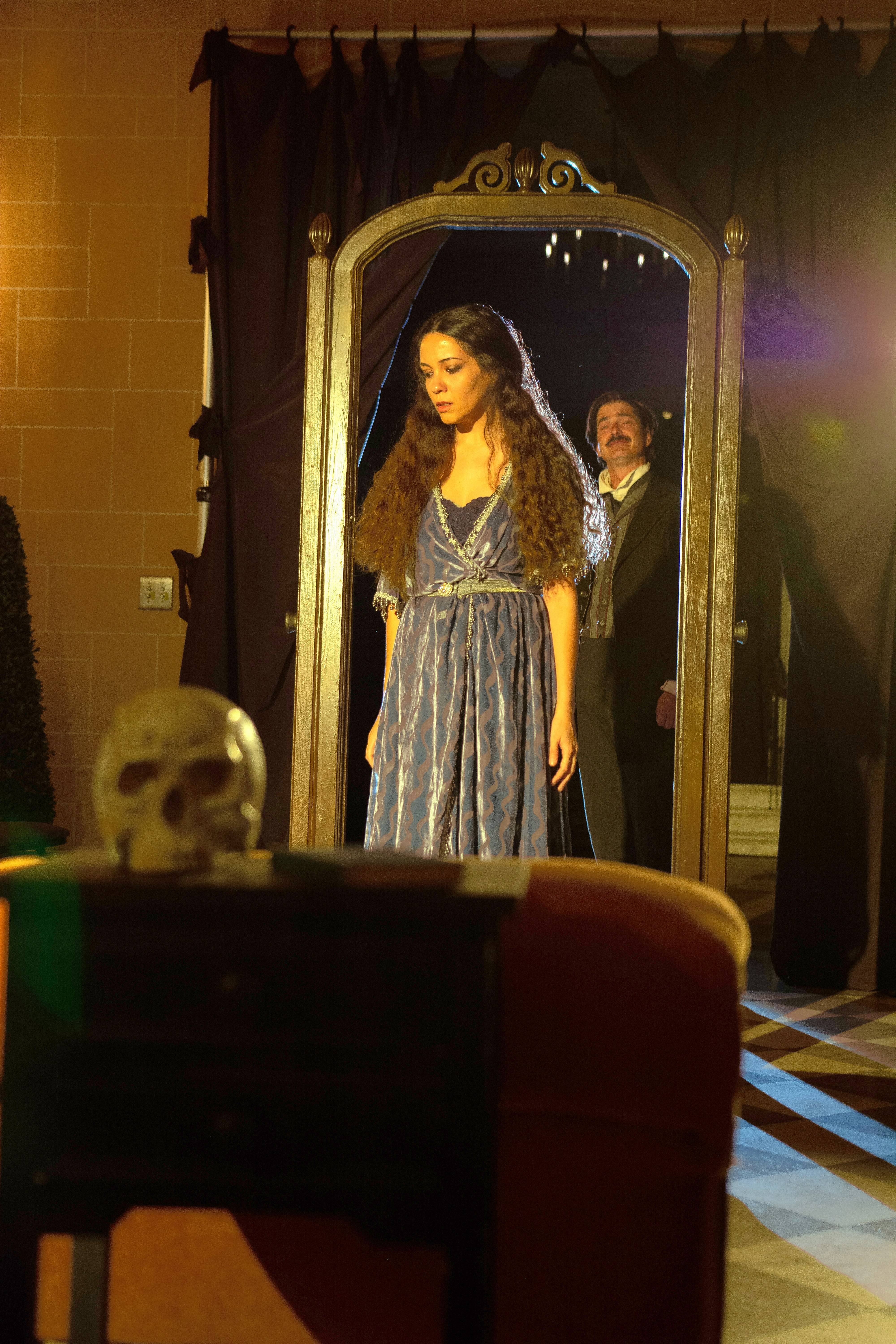 "Joan Nahid, foreground, plays the mysterious Ligeia, who from the grave haunts her husband, Verdon (Christian Gray), background, in First Folio Theatre's ""The Madness of Edgar Allan Poe: A Love Story."""