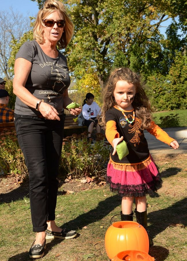 Saphira Does of Elgin tries the pumpkin toss with the help of Terri Blanke during Barrington's Scarecrow Festival in 2017.