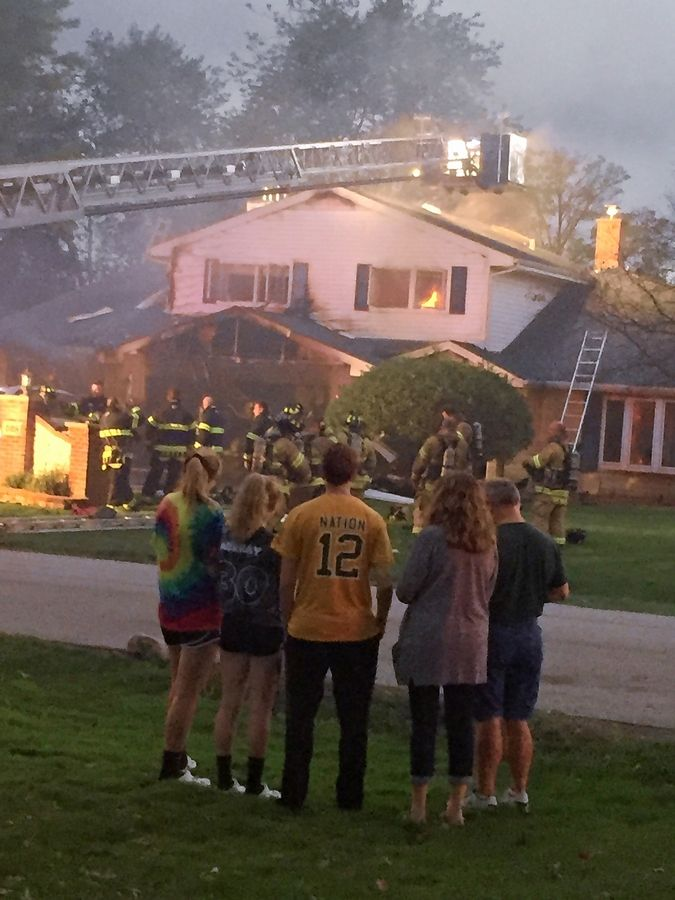Neighbors watch as a house on the 500 block of Crest Avenue in Elk Grove Village burns Wednesday evening.
