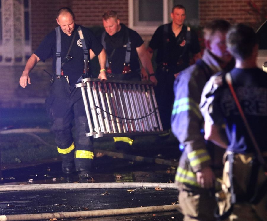 Elk Grove Village firefighters on Wednesday night finish putting out a house fire on Crest Avenue near Ridge Avenue and Landmeier Road.