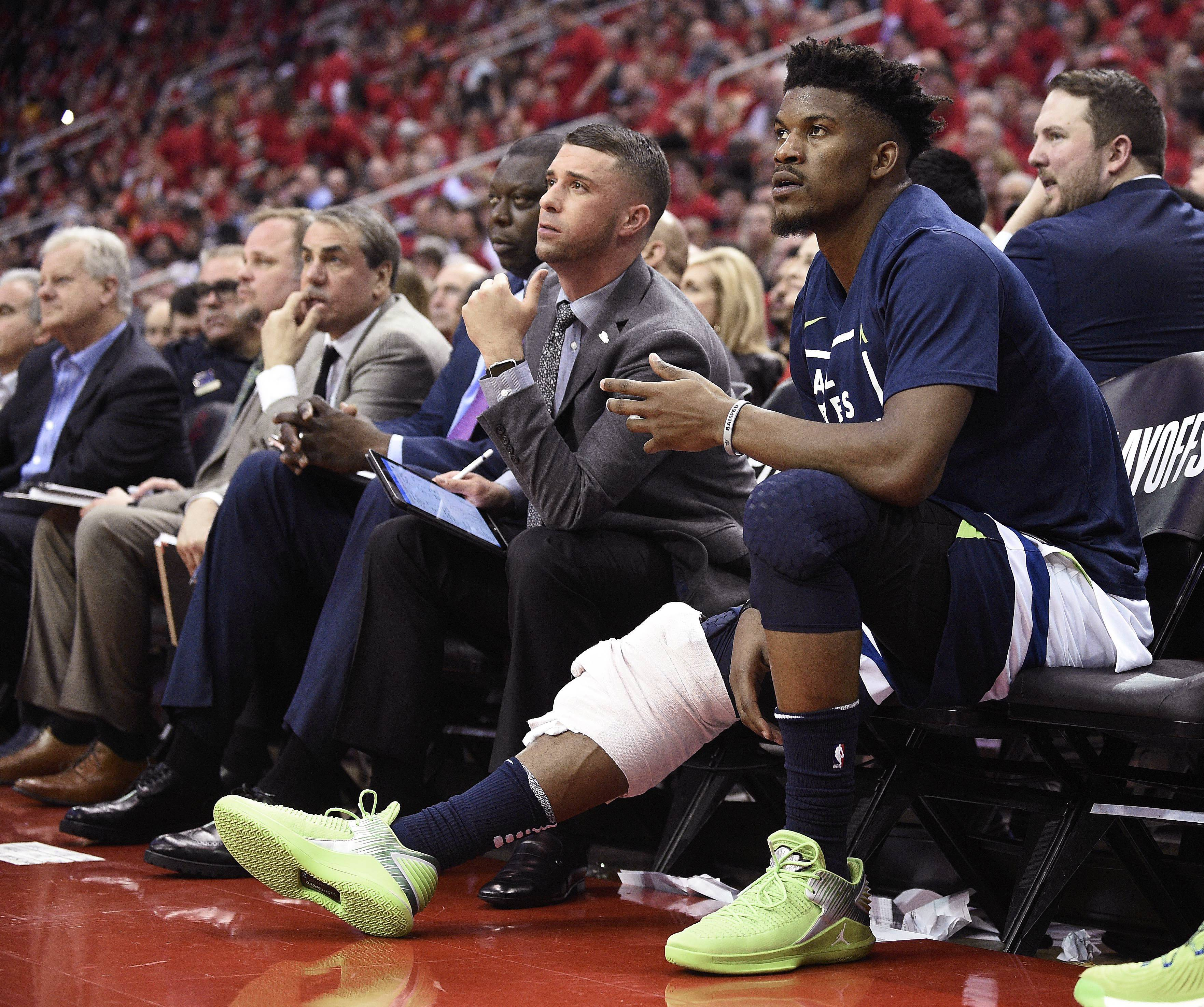 In this April 25, 2018, file photo, Minnesota Timberwolves guard Jimmy Butler, right, watches from the bench during the second half in Game 5 of the team's first-round NBA basketball playoff series against the Houston Rockets, in Houston. With Butler's status still unresolved, coach Tom Thibodeau and the Timberwolves head toward the season coming off the franchise's first playoff appearance in 14 years but carrying yet a still-cloudy outlook despite the super-max contract Karl-Anthony Towns.