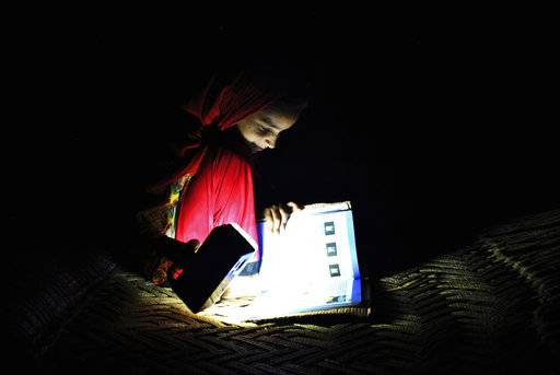 In this Friday, August 10, 2018, photo, Ansa Khan studies with a flash light during a power outage in Mardan, Pakistan. Ansa enjoys her school, saying her favorite subject is Islamiat. Electricity is not always reliable in Ansa's Toru village and she is often forced to study by flashlight.