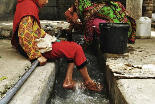 "In this Monday, July 9, 2018, photo, Ansa Khan cools her feet with running water just adjacent to her home while her mother and sister are busy in their household activities and washing clothes and utensils in Mardan, Pakistan. Since 2012 the United Nations has reserved Oct. 11 as the International day of the Girl Child ""to recognize girls' rights and the unique challenges girls face around the world.� This year the theme is employable skills for girls, particularly in the poorer economies."