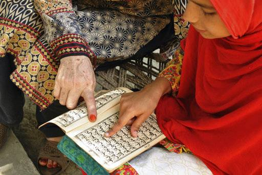 In this Tuesday, June 26, 2018, photo, Ansa Khan first's work in the morning after breakfast is to recite the Quran with her religious teacher in her village in Mardan, Pakistan. After that her day is a whirl of chores, school, studying and the occasional moments stolen away to play marbles.