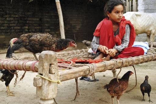 "In this Monday, July 9, 2018, photo, Ansa Khan feeds her small chicks and hens at her home in Mardan, Pakistan. Since 2012 the United Nations has reserved Oct. 11 as the International day of the Girl Child ""to recognize girls' rights and the unique challenges girls face around the world.� This year the theme is employable skills for girls, particularly in the poorer economies."