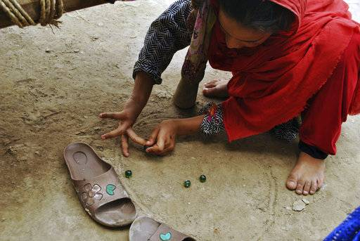 In this Friday, August 10, 2018, photo,  in Mardan, Pakistan, Ansa Khan plays marbles on the dirt floor of her home. This is the most famous game in rural areas of Khyebr Pakhtunkhwa Province, which is played by small girls and boys both. (AP Photo/Saba Rehman).
