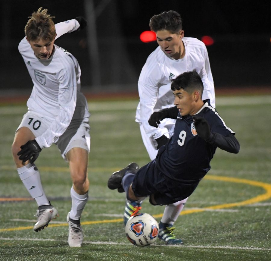 Buffalo Grove's Kevin Eloiza is fouled as he is sandwiched by Fremd's Vince Daidone and Aiden Johnston Thursday in a Mid-Suburban League Soccer Bowl boys soccer game in Buffalo Grove.