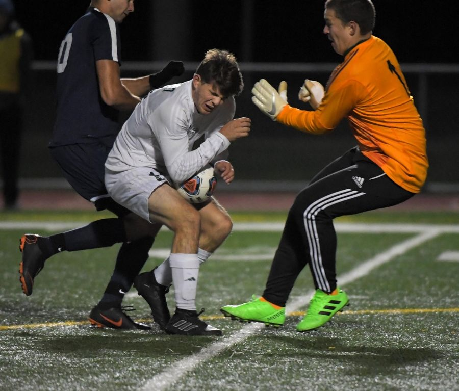 Fremd's Jake Schoffstall prepares for a collision with teammate goalkeeper Artur Cholewa as Buffalo Grove's Jonathan Peici forces the action Thursday in a Mid Suburban League Soccer Bowl boys soccer game in Buffalo Grove.