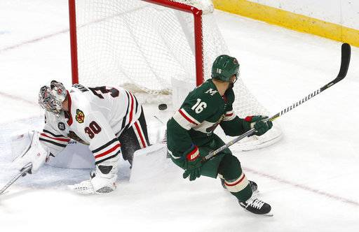 Minnesota Wild's Jason Zucker, right, watches his overtime goal against Chicago Blackhawks goalie Cam Ward in an NHL hockey game Thursday, Oct. 11, 2018, in St. Paul, Minn. The Wild won 4-3. It was Zucker's second goal of the game.