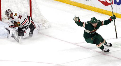 Minnesota Wild's Jason Zucker, right, celebrates his overtime goal against Chicago Blackhawks goalie Cam Ward in an NHL hockey game Thursday, Oct. 11, 2018, in St. Paul, Minn. The Wild won 4-3. It was Zucker's second goal of the game.