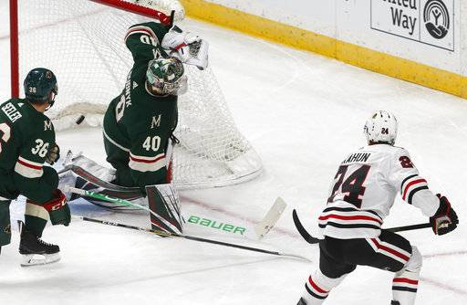 Chicago Blackhawks' Dominik Kahun, right, of the Czech Republic, scores a goal against Minnesota Wild goalie Devan Dubnyk during the first period of an NHL hockey game Thursday, Oct. 11, 2018, in St. Paul, Minn.