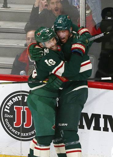 Minnesota Wild's Jason Zucker, left, and Eric Staal celebrate a goal by Staal against Chicago Blackhawks goalie Cam Ward during the second period of an NHL hockey game Thursday, Oct. 11, 2018, in St. Paul, Minn. Zucker also scored with seconds to play in the period to tie the game.