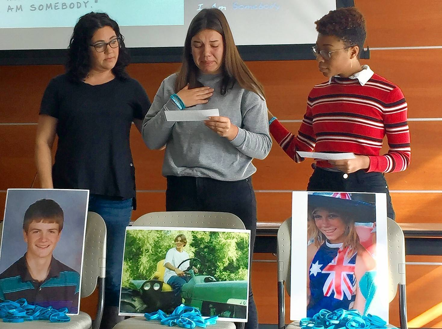 Jenn Djordjevic, left, Jaidyn Karskens, center, and Kailah Peters read the stories of children who were victims of bullying and who died by suicide at a presentation Saturday in Hoffman Estates.