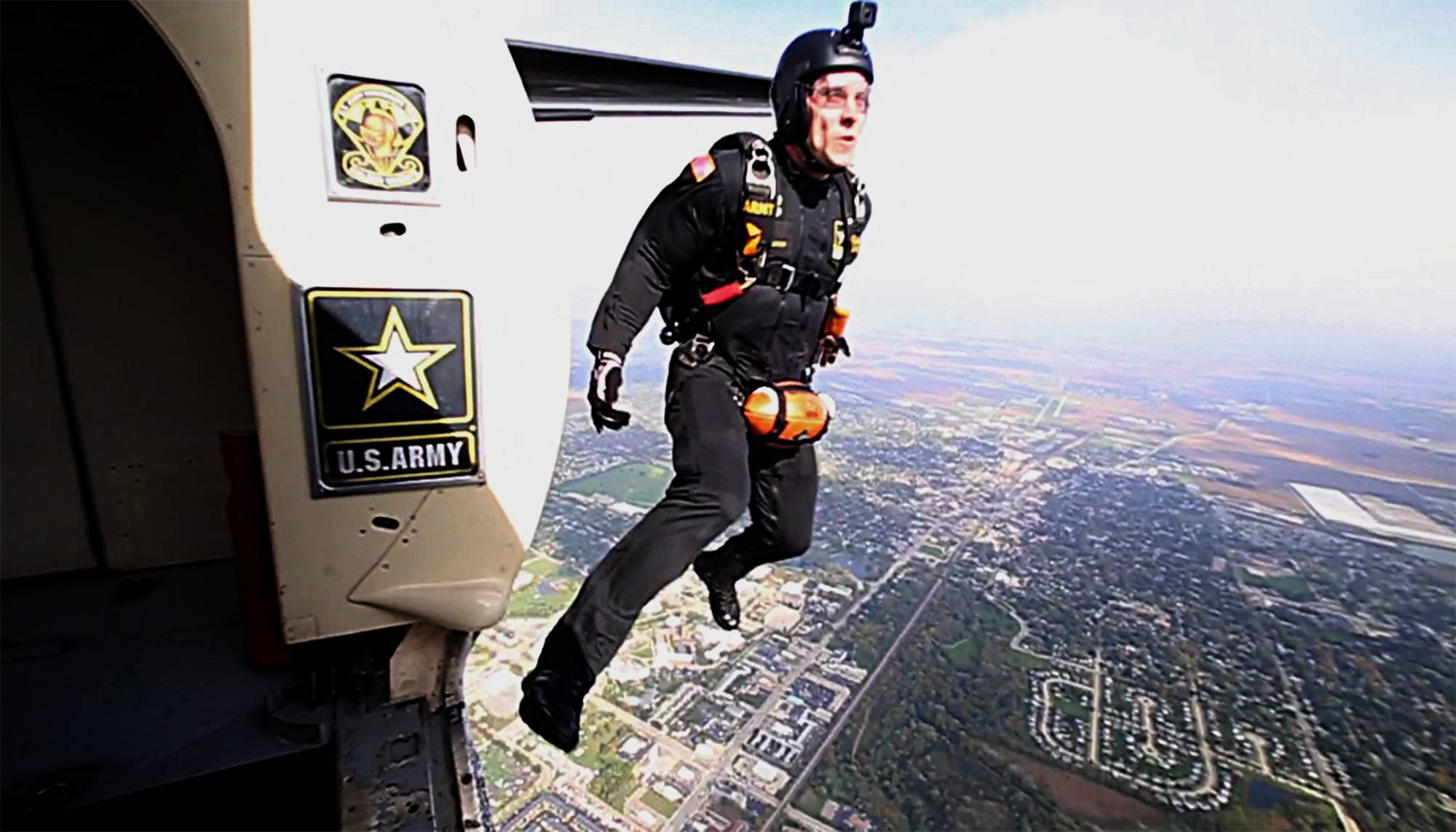 U.S. Army Golden Knight parachutist SFC Keith Pierce leaps toward Huskie Stadium in DeKalb to deliver the game ball for NIU's 112th homecoming game Saturday.