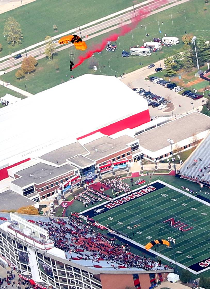 Members of the U.S. Army Golden Knight parachute team leap toward Huskie Stadium in DeKalb to deliver the game ball for NIU's 112th homecoming game Saturday.