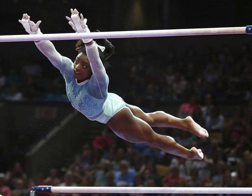 FILE - In this Aug. 19, 2018, file photo, Simone Biles competes on the uneven bars at the U.S. Gymnastics Championships in Boston. Biles is upset about an anti-Nike tweet last month from USA Gymnastics interim president and CEO Mary Bono. Bono was appointed Friday, Oct. 12, to hold the position while USA Gymnastics searches for a permanent successor to Kerry Perry, who resigned under pressure from the United States Olympic Committee in September after spending nine months on the job.