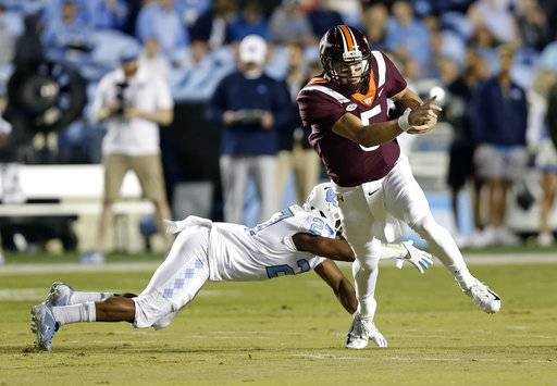 Virginia Tech quarterback Ryan Willis (5) breaks a tackle-attempt by North Carolina's Chris Collins (17) during the first half of an NCAA college football game in Chapel Hill, N.C., Saturday, Oct. 13, 2018. Willis scored on the play.