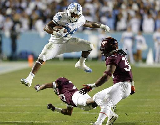 North Carolina's Antonio Williams (24) jumps over Virginia Tech's Jovonn Quillen as Virginia Tech's Rico Kearney looks for a tackle during the first half of an NCAA college football game in Chapel Hill, N.C., Saturday, Oct. 13, 2018.