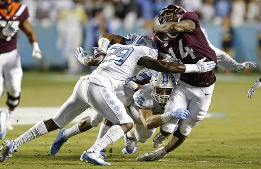 Virginia Tech's Damon Hazelton (14) is tackled by North Carolina's J.K. Britt (29) and Cole Holcomb (36) during the first half of an NCAA college football game in Chapel Hill, N.C., Saturday, Oct. 13, 2018.