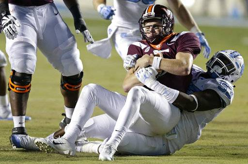 North Carolina's Malik Carney (53) tackles Virginia Tech quarterback Ryan Willis (5) during the first half of an NCAA college football game in Chapel Hill, N.C., Saturday, Oct. 13, 2018.