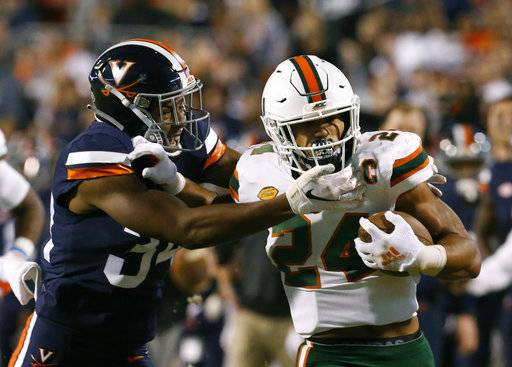 Miami running back Travis Homer (24) pushes off Virginia cornerback Bryce Hall (34) during the first half of an NCAA college football game in Charlottesville, Va., Saturday, Oct. 13, 2018.
