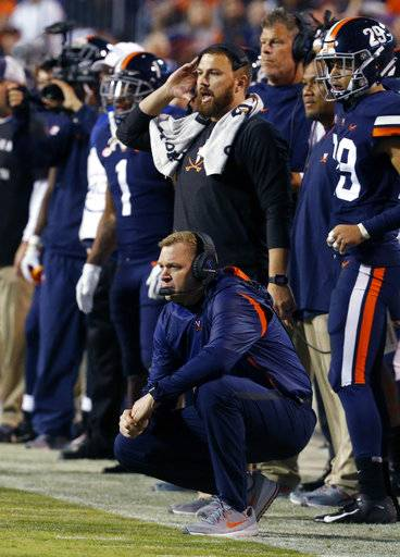 Virginia head coach Bronco Mendenhall, kneeling, watches a field goal attempt during the first half of an NCAA college football game in Charlottesville, Va., Saturday, Oct. 13, 2018.