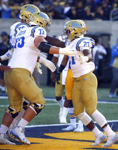 UCLA running back Joshua Kelley, right, celebrates with Jake Burton (73) after scoring a touchdown against California during the first half of an NCAA college football game Saturday, Oct. 13, 2018, in Berkeley, Calif.