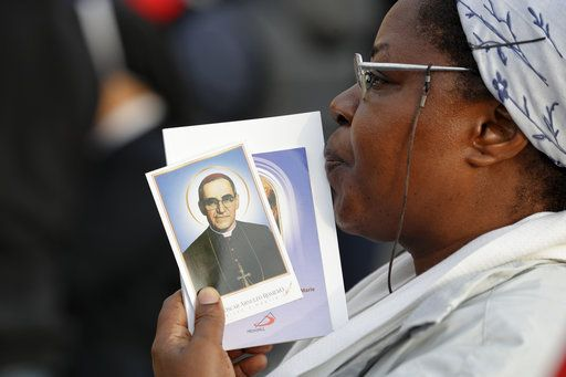 A woman holds a picture of martyred Salvadoran Archbishop Oscar Romero, in St. Peter's Square at the Vatican, Sunday, Oct. 14, 2018. Pope Francis canonizes two of the most important and contested figures of the 20th-century Catholic Church, declaring Pope Paul VI and the martyred Salvadoran Archbishop Oscar Romero as models of saintliness for the faithful today.
