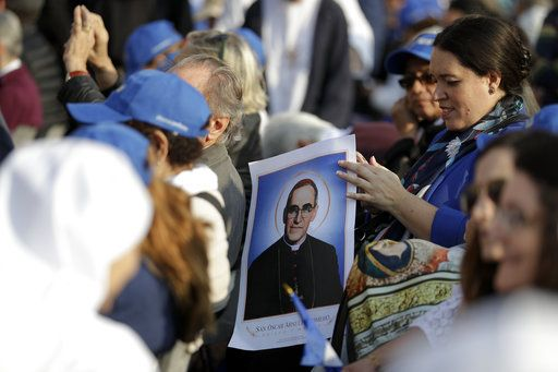 A woman holds a picture of martyred Salvadoran Archbishop Oscar Romero prior to a canonization ceremony in St. Peter's Square at the Vatican, Sunday, Oct. 14, 2018. Pope Francis canonizes two of the most important and contested figures of the 20th-century Catholic Church, declaring Pope Paul VI and the martyred Salvadoran Archbishop Oscar Romero as models of saintliness for the faithful today.