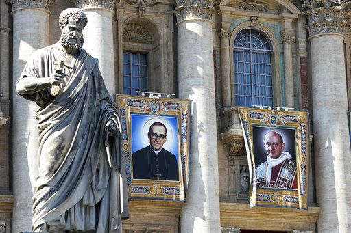 The tapestries of Roman Catholic Archbishop Oscar Romero, left, and Pope Paul VI hang from a balcony of the facade of St. Peter's Basilica at the Vatican, Saturday, Oct. 13, 2018. Pope Francis will canonize two of the most important and contested figures of the 20th-century Catholic Church, declaring Pope Paul VI and the martyred Salvadoran Archbishop Oscar Romero as models of saintliness for the faithful today.