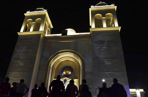 Images of El Salvador's martyred Salvadoran Archbishop Oscar Romero are projected on the Metropolitan Cathedral where his remains are entombed in San Salvador, El Salvador, early Sunday, Oct. 14, 2018, as people hold a vigil and watch live images from the Vatican where he is declared a Saint. For many in San Salvador, it was the culmination of a fraught and politicized campaign to have the church formally honor a man who publicly denounced the repression by El Salvador's military dictatorship at the start of the country's 1980-1992 civil war.