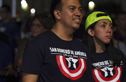 "A couple wears T-shirts that read in Spanish ""Saint Romero of America. Feel with the church,"" as they watch live tv images from the Vatican where El Salvador's martyred Salvadoran Archbishop Oscar Romero is declared a Saint, during a vigil outside the cathedral where Romero's remains are entombed in San Salvador, El Salvador, early Sunday, Oct. 14, 2018. For many in San Salvador, it was the culmination of a fraught and politicized campaign to have the church formally honor a man who publicly denounced the repression by El Salvador's military dictatorship at the start of the country's 1980-1992 civil war."