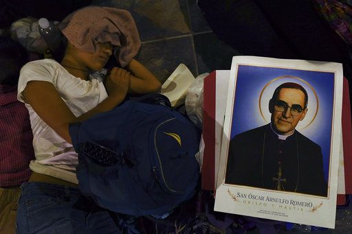 A woman waits all night to watch live tv images from the Vatican where El Salvador's martyred Salvadoran Archbishop Oscar Romero will be declared a Saint, where she and others are gathered outside the cathedral where Romero's remains are entombed in San Salvador, El Salvador, early Sunday, Oct. 14, 2018. For many in San Salvador, it was the culmination of a fraught and politicized campaign to have the church formally honor a man who publicly denounced the repression by El Salvador's military dictatorship at the start of the country's 1980-1992 civil war.