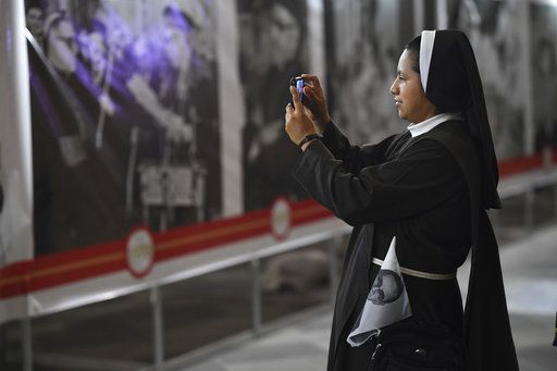 A nun takes pictures of a photo exhibit on El Salvador's martyred Salvadoran Archbishop Oscar Rome, outside the cathedral where Romero's remains are entombed in San Salvador, El Salvador, early Sunday, Oct. 14, 2018, as people hold an overnight vigil and prepare to watch live images from the Vatican that will declare him a Saint. For many in San Salvador, it was the culmination of a fraught and politicized campaign to have the church formally honor a man who publicly denounced the repression by El Salvador's military dictatorship at the start of the country's 1980-1992 civil war.