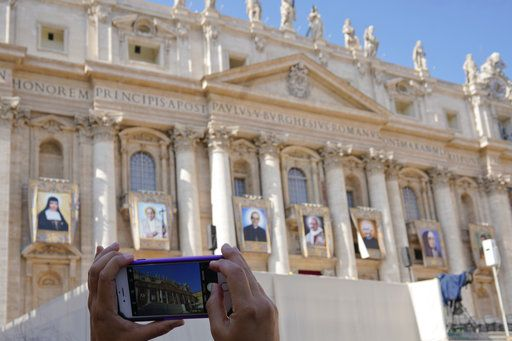 A woman takes photos of tapestries of Roman Catholic Archbishop Oscar Romero, 3rd from left, and Pope Paul VI, 4th from left, hanging from a balcony of the facade of St. Peter's Basilica at the Vatican, Saturday, Oct. 13, 2018. Pope Francis will canonize two of the most important and contested figures of the 20th-century Catholic Church, declaring Pope Paul VI and the martyred Salvadoran Archbishop Oscar Romero as models of saintliness for the faithful today.