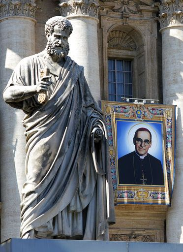 The tapestry of Roman Catholic Archbishop Oscar Romero hangs from a balcony of the facade of St. Peter's Basilica at the Vatican, Saturday, Oct. 13, 2018. Pope Francis will canonize two of the most important and contested figures of the 20th-century Catholic Church, declaring Pope Paul VI and the martyred Salvadoran Archbishop Oscar Romero as models of saintliness for the faithful today.