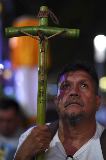 Evelio Rivas holds a cross made of bamboo, symbolizing El Salvador's martyred Salvadoran Archbishop Oscar Romero, as he and others stay up all night to watch live tv images from the Vatican where Romero is declared a Saint, outside the cathedral where Romero's remains are entombed in San Salvador, El Salvador, early Sunday, Oct. 14, 2018. For many in San Salvador, it was the culmination of a fraught and politicized campaign to have the church formally honor a man who publicly denounced the repression by El Salvador's military dictatorship at the start of the country's 1980-1992 civil war.