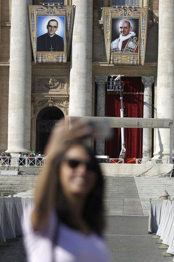 FILE - In this Friday, Oct. 12, 2018 filer, the tapestries of Roman Catholic Archbishop Oscar Romero, left, and Pope Paul VI hang from a balcony of the facade of St. Peter's Basilica at the Vatican. Pope Francis will canonize two of the most important and contested figures of the 20th-century Catholic Church, declaring Pope Paul VI and the martyred Salvadoran Archbishop Oscar Romero as models of saintliness for the faithful today. Sunday's ceremony is likely to be emotional for Francis, since he was greatly influenced by both men and privately told confidantes he wanted them made saints during his papacy.